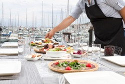 Restaurant at sea shore against blue water and Yacht Port of Aegean coast on Cesme. Marble Table with plate of beef appetizers, cheese, bread, Carpaccio, raki, ouzo and. Copy space for text area