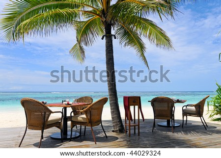 Restaurant by the ocean under palm tree stock photo 44029324