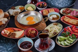 Restaurant concept; Traditional Turkish spreader breakfast  on the black wooden table, top view. Healthy Turkish breakfast in the bright morning; copy space for text.