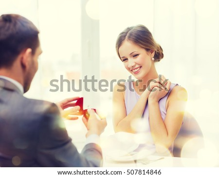 restaurant, couple and holiday concept - excited young woman looking at boyfriend with engagement ring at restaurant