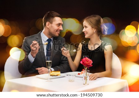 restaurant couple and holiday concept smiling couple eating dessert at restaurant