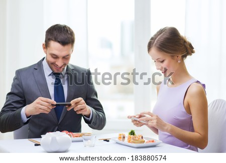 restaurant, couple, technology and holiday concept - smiling couple taking picture of sushi with smartphone camera at restaurant