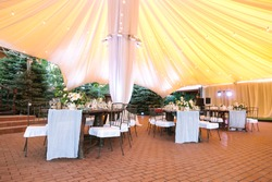 restaurant, engagement, interior concept. under huge yellow tent there are wooden tables in vintage style decorated with bunches of flowers and snowy white tablewares