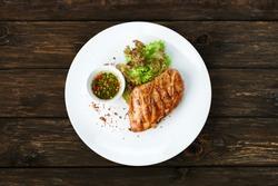 Restaurant food - chicken fillet grilled steak at wooden table