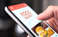 Restaurant food delivery service in phone. Take away menu in digital mobile app. Man ordering takeout pizza or burger online. Fast lunch delivered home. Person using smartphone and mockup application.