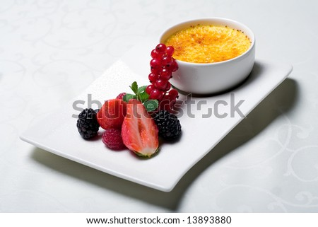 Restaurant food. Restaurant dessert. Sweet appetizer, creme brulee with fresh berries. Creative restaurant food. French cuisine dessert. Creme Caramel with raspberry, strawberry, blackberry. Closeup