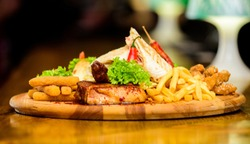 Restaurant food. Wooden board with lot french fries fish sticks burrito and meat steak served with salad. Pub menu snack. High calorie snack for group friends. Tasty delicious snacks. Snack for beer.