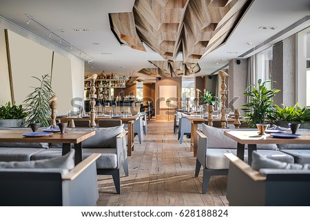 Restaurant in a modern style with textured walls and a parquet. There are gray sofas with tables, decorative wooden poles with birds, bar, plants. On ceiling there are wooden geometric constructions.