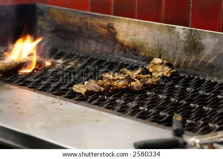 Restaurant indoor bbq with meat on a flame grill
