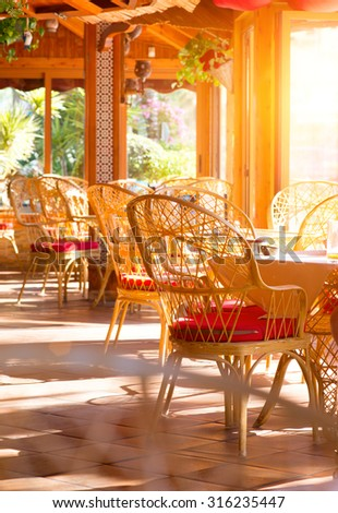 Restaurant interior. Fashioned cafe terrace. View of an sunny empty summer coffee terrace with tables and wicker chairs. Interior of cozy restaurant decorated with plant. Vertical photo