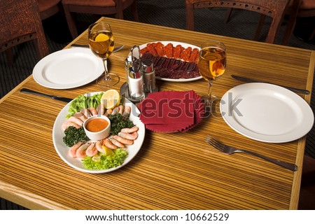 restaurant interior - laying table with white wine and shrimps