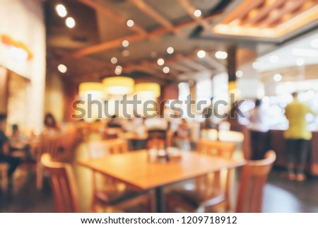 Restaurant interior with customer and wood table blur abstract background with bokeh light #1209718912