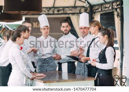 Restaurant manager and his staff in terrace. interacting to head chef in restaurant #1470477704