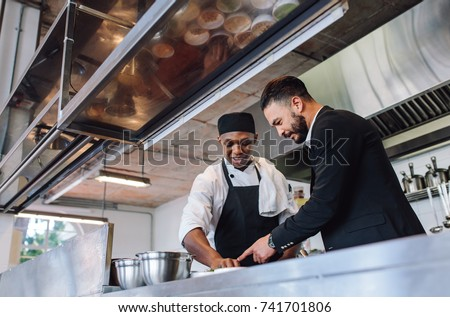 Restaurant manager discussing with chef in kitchen. Cook preparing a dish with restaurant owner standing by.