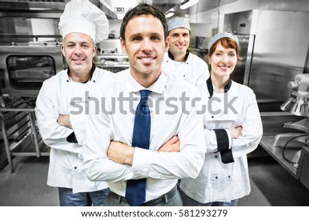 Restaurant manager posing in front of team of chefs smiling at camera #581293279