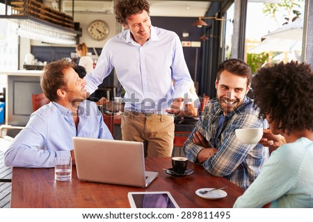 Restaurant manager talking to customers at their table