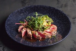 Restaurant menu. Salad with tuna, cucumber, herbs and micro greens. With sauce. Red tuna with sesame seeds. The blue plate. Red, green, blue. Dark background