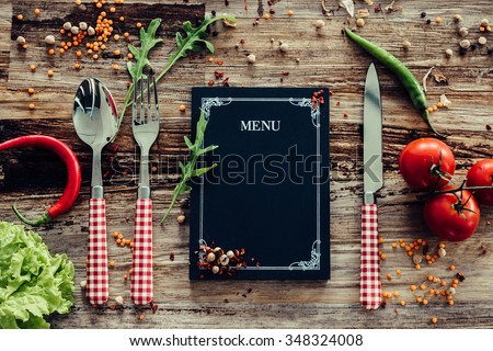 Restaurant menu. Top view of chalkboard menu laying on the rustic wooden desk with vegetables around
