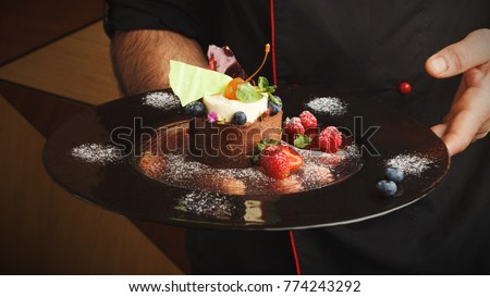 Restaurant mousse dessert in chef hands. Chocolate and vanilla souffle on walnut biscuit served at gray table on glass plate finely decorated with fresh berries and mint. Haute cuisine concept