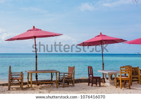 Restaurant on the tropical beach with pink umbrellas, tables and chairs #1076416070