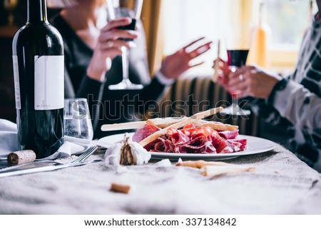 Restaurant or bar table with plate of appetizers and wine. Two people talking on background