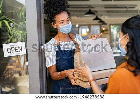 Restaurant owner working only with take away orders during corona virus outbreak. Young black woman wearing face mask giving takeout meal to customer outside her cafeteria. Customer pick up take-away.