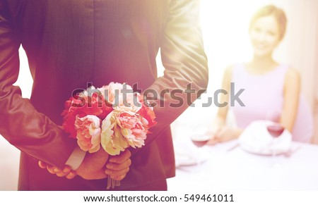 restaurant, people, celebration and holiday concept - close up of man hiding flowers behind from woman at restaurant