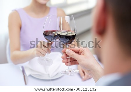 restaurant, people, celebration and holiday concept - close up of young couple with glasses of red wine at restaurant #305123132
