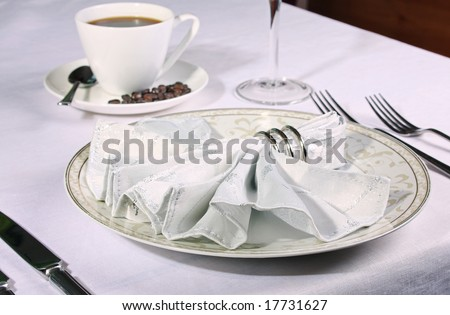 Restaurant place setting with fan napkin in ring and warm coffee in background
