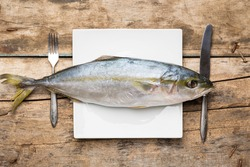 Restaurant seafood menu background. Fresh tuna on white dish with silverware on wooden table. Top view image