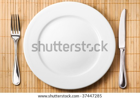 Restaurant serving (metal fork, knife and ceramic white plate)