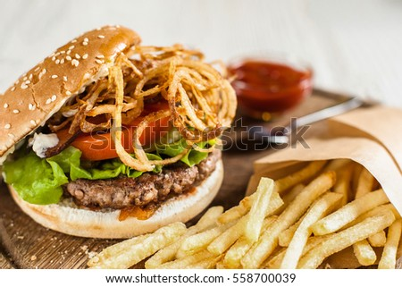 Restaurant serving of burger with fries and ketchup. Side view on catering platter with traditional american snack. Fast junk food, dining, fat eating concept #558700039