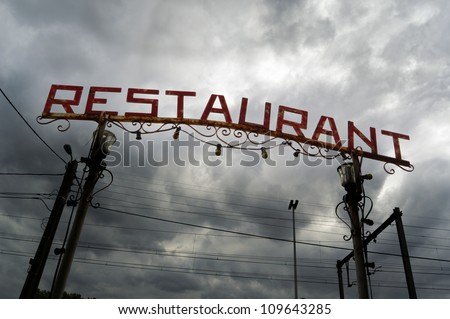Restaurant Sign - Old entrance to a Restaurant with ominous dark cloudy sky in background