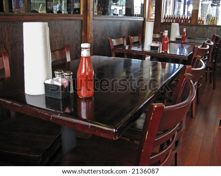 Restaurant table and chairs with paper towels and condiments.