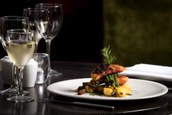 Restaurant table set  main dish steak fish cuisine fine dinning white wine glass cooler  candle light wooden table atmosphere menu