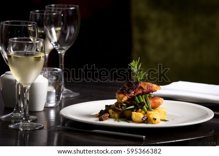 Restaurant table set  main dish steak fish cuisine fine dinning white wine glass cooler  candle light wooden table atmosphere menu