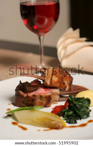 restaurant table with a plate of lamb meal - stock photo