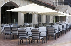Restaurant tables, chairs and white umbrellas.