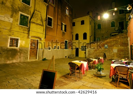 Restaurant tables on quiet Venetian piazza at night
