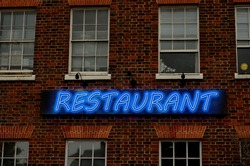Restaurant text is written on an old building using image processing software.