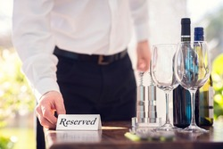 Restaurant waiter placing a reserved table sign with place setting and wine glasses ready for a party