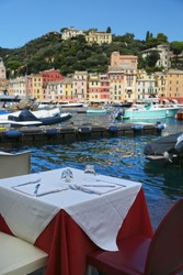 Restaurant with a view in Portofino, Italy. Table serving for dinner with glasses up side down on background of marina, small boats and sea in warm summer day