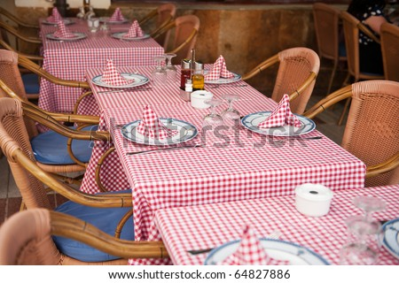 restaurant with rattan with checked table cloths at the terrace