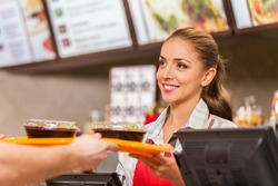 Restaurant worker serving two fast food meals with smile. woman holding tray with salads at fast food restaurant