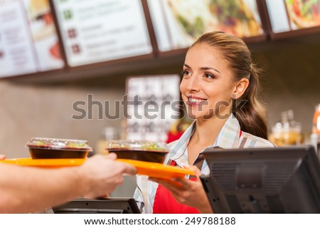 Restaurant worker serving two fast food meals with smile. woman holding tray with salads at fast food restaurant #249788188