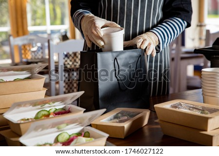 Restaurant worker wearing protective mask and gloves packing food boxed take away. Food delivery services and Online contactless food shopping.  Foto d'archivio ©