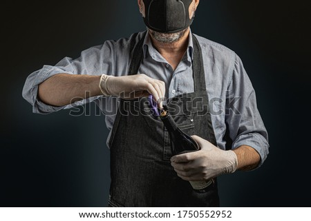 Restaurants reopening after coronavirus quarantine. Man bartender uncorking a bottle of red wine wearing gloves and safety mask. Unrecognizable people face. Stock photo ©