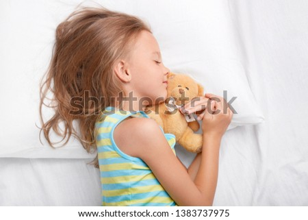 Restful female child with light messy hairstyle, lies on side, keeps her favourite teddy bear in hands, enjoys healthy long sleep at night, soft bedclothes, dressed in nightwear. Children and rest #1383737975