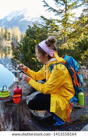 Restful female traveler makes coffee on camping stove, poses near stump, has break after wandering, poses against wonderful nature with lake, mountains and fir trees, enjoys life and traveling #1413558164