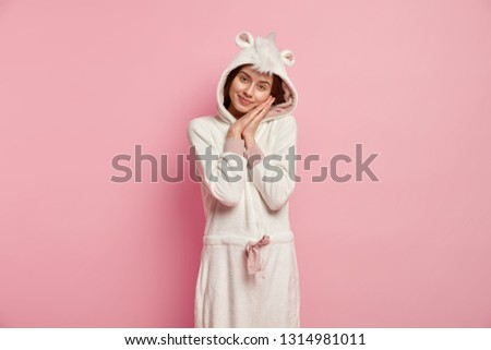Restful girl leans at hands, enjoys good sleep, wears funny soft domestic outfit, looks at camera with tender look, poses over pink background, has nice rest in calm atmosphere. Bedding concept #1314981011